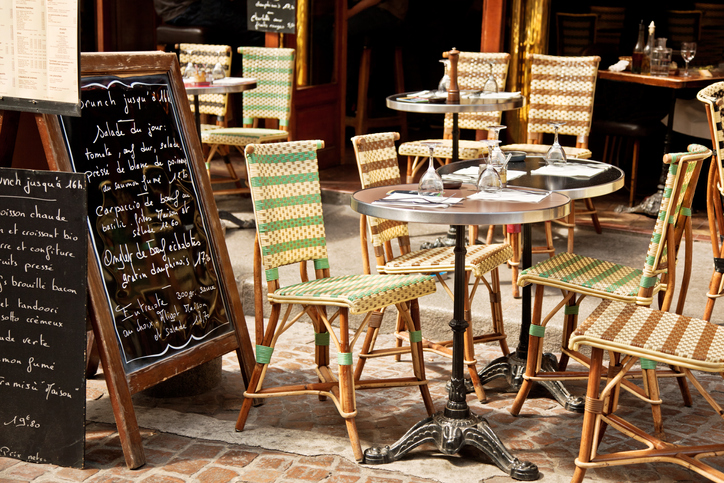 set table on a Paris sidewalk next to menu board - why do i get a gluten reaction with american vs european wheat overseas